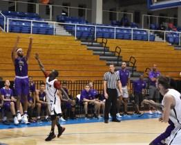 JMU freshman guard Matt Lewis launches a three-pointer over Carleton.
