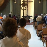 A view up the center aisle of the torch, looking toward the altar, with two acolytes in the foreground.