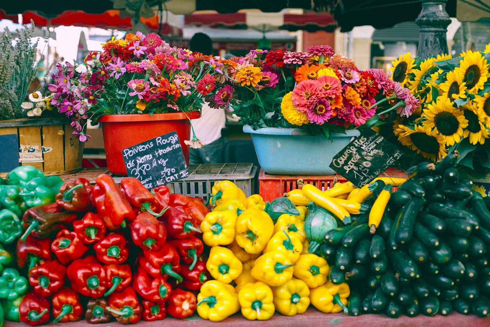 assorted vegetables and blooming flowers at market