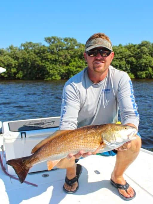 the captain holding a redfish