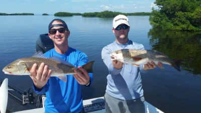 guys holding caught redfish