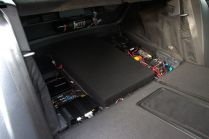 The front of the electronics panel is hidden by the folding section of the factory trunk floor...