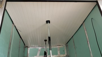 I used a pair of cargo stabilization bars to hold up the ceiling while cutting out the roof fan opening...