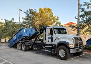 an image of the SteelSmith roll off truck picking up a dumpster for transport