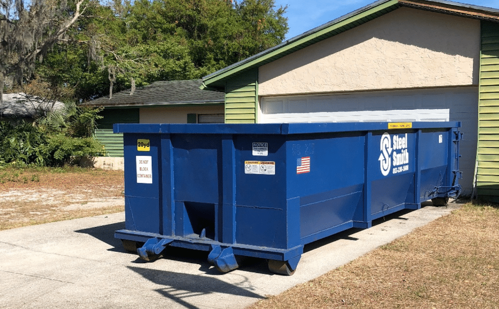 A photo of a dumpster in a driveway of a residential dumpster rental project