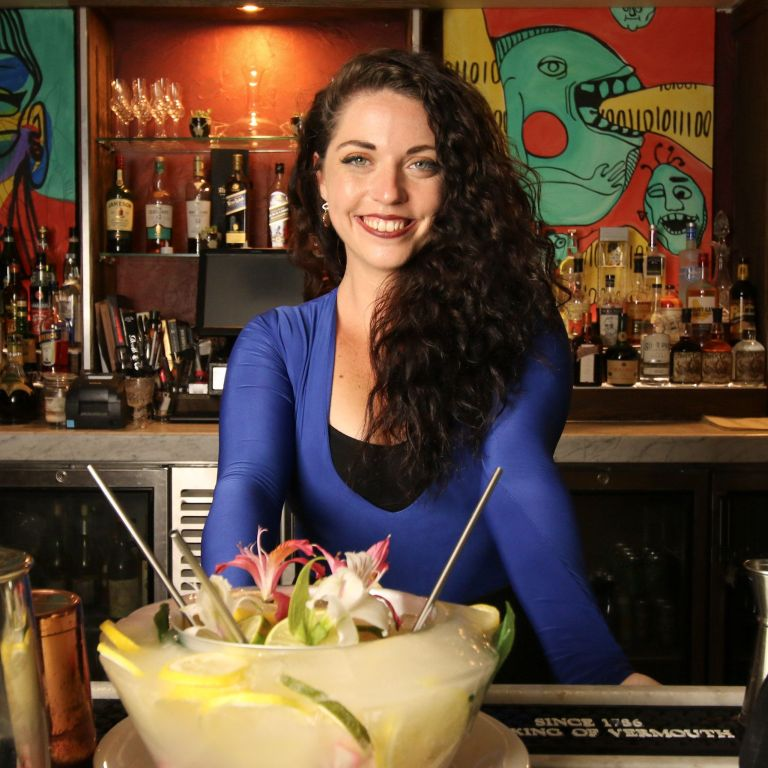 Woman bartender posing behind a bar with large, mixed cocktail on the bar table in front of her
