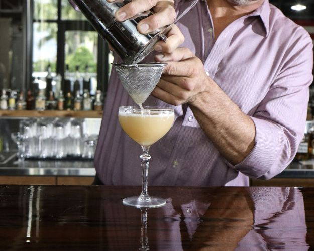 bartender pouring cocktail at a bar