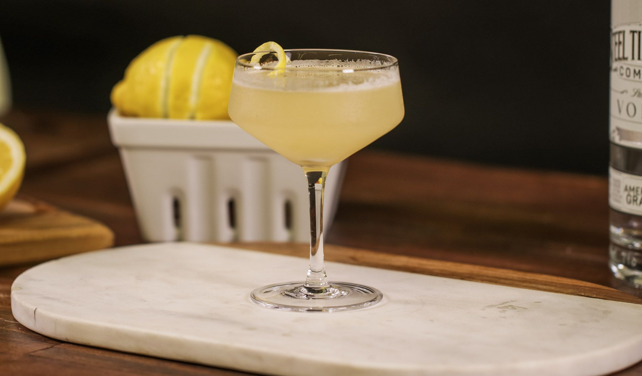 Coupe glass sitting on marble cutting board filled with vodka and lemon juice with a basket of lemons in the background