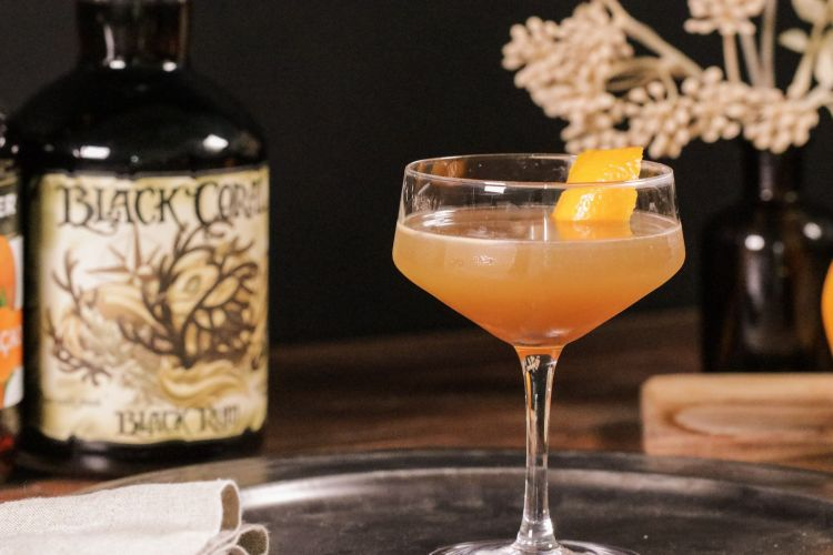 Rum Sidecar cocktail sitting on a metal serving plate with tan flowers in the background
