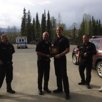 Blayde Briske receives his service plaque from Chief Mitch Flynn