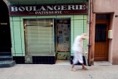 Old woman in white walking past a green-walled boulangerie