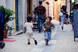 Two young boys running and playing in an alleyway