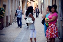 A group of woman stand about chatting in an alleyway