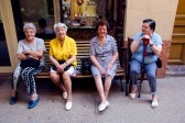 Four old woman rest on a bench