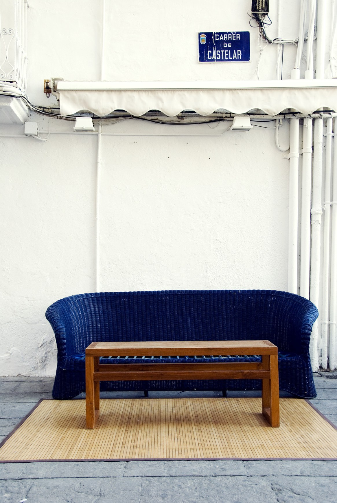 Blue sofa and brown table against a white wall