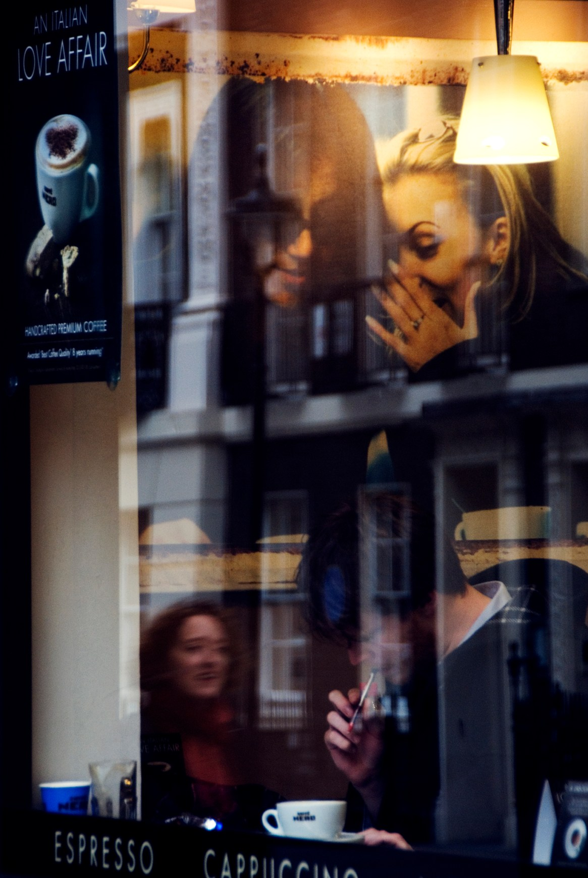 A man in a coffee shop under a sign of two whispering characters, superimposed over a reflection of a woman walking by