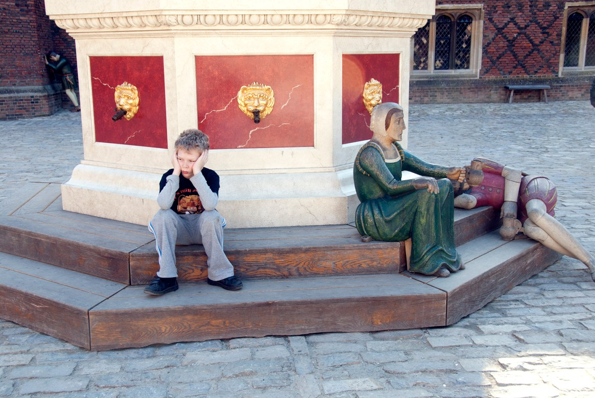 A distressed-looking boy perches on a step next to some wooden figurines at Hampton Court Palance
