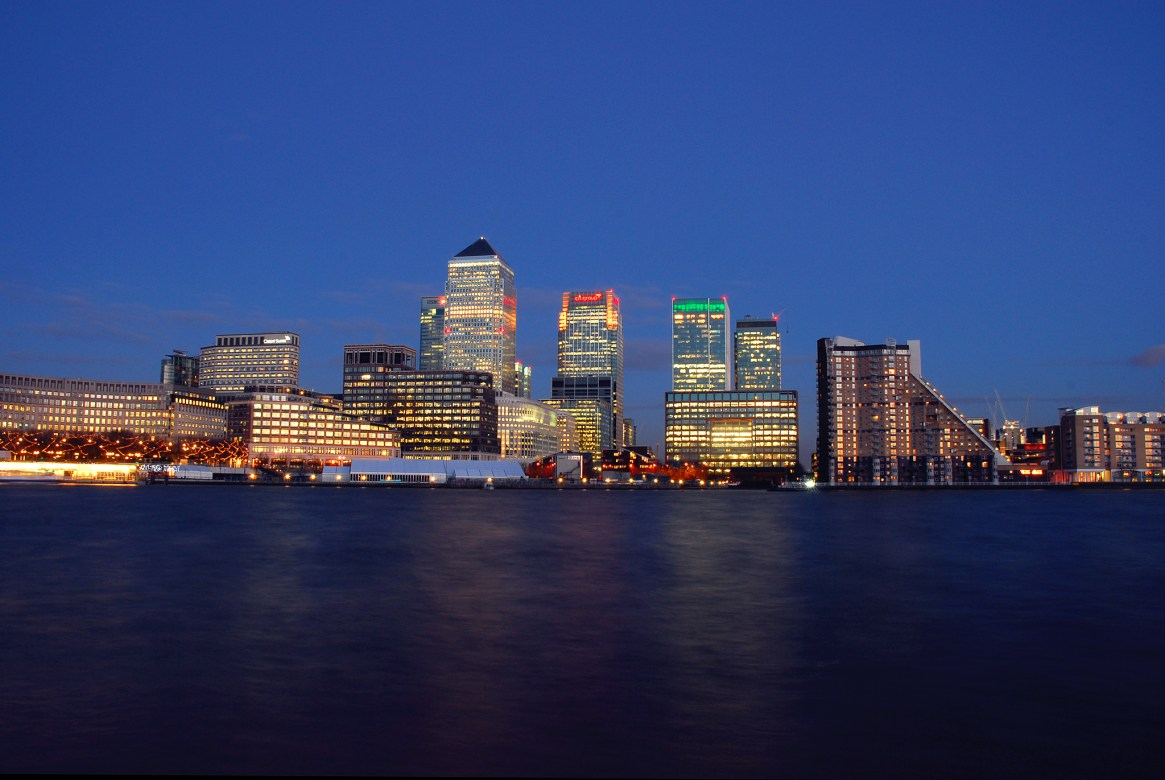 The Canary Wharf financial district lit up against a dark blue sky at sunset