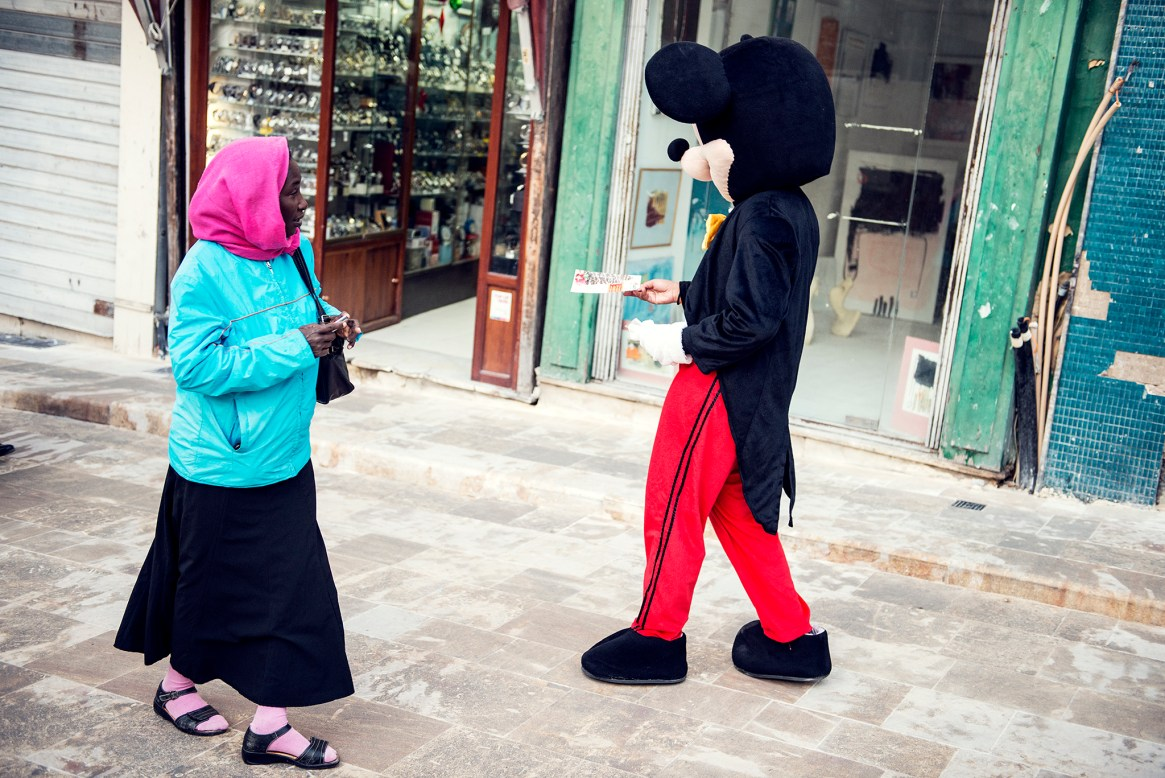 A woman in purple headscarf walks past a person dressed up as Mickey Mouse in Valletta, Malta