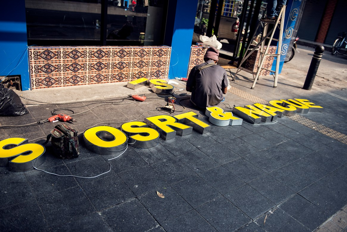 A man hunches in front of a set of neon letters, neatly arranged on the pavement and ready for installation