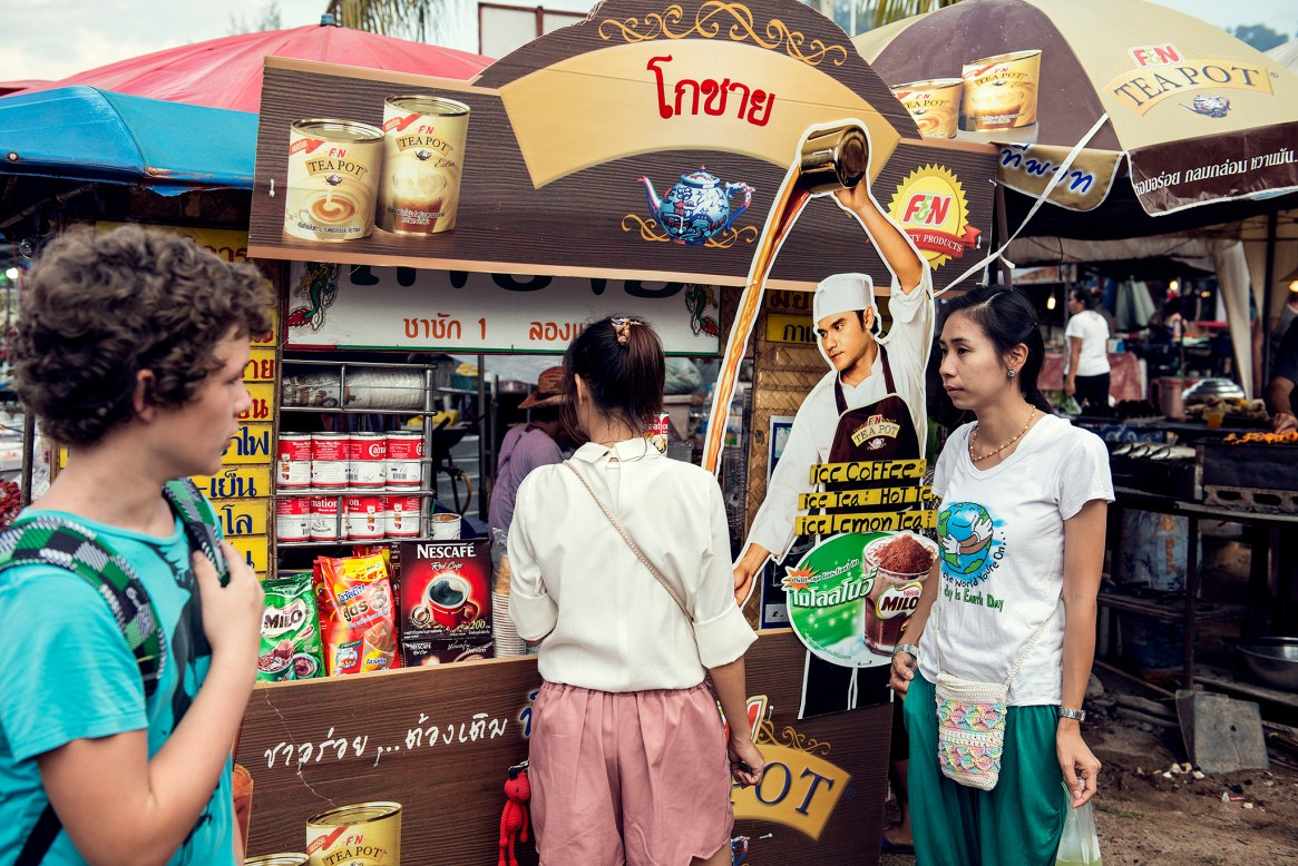 A young man looks at two women buying drinks from an coffee stand in a Thai market