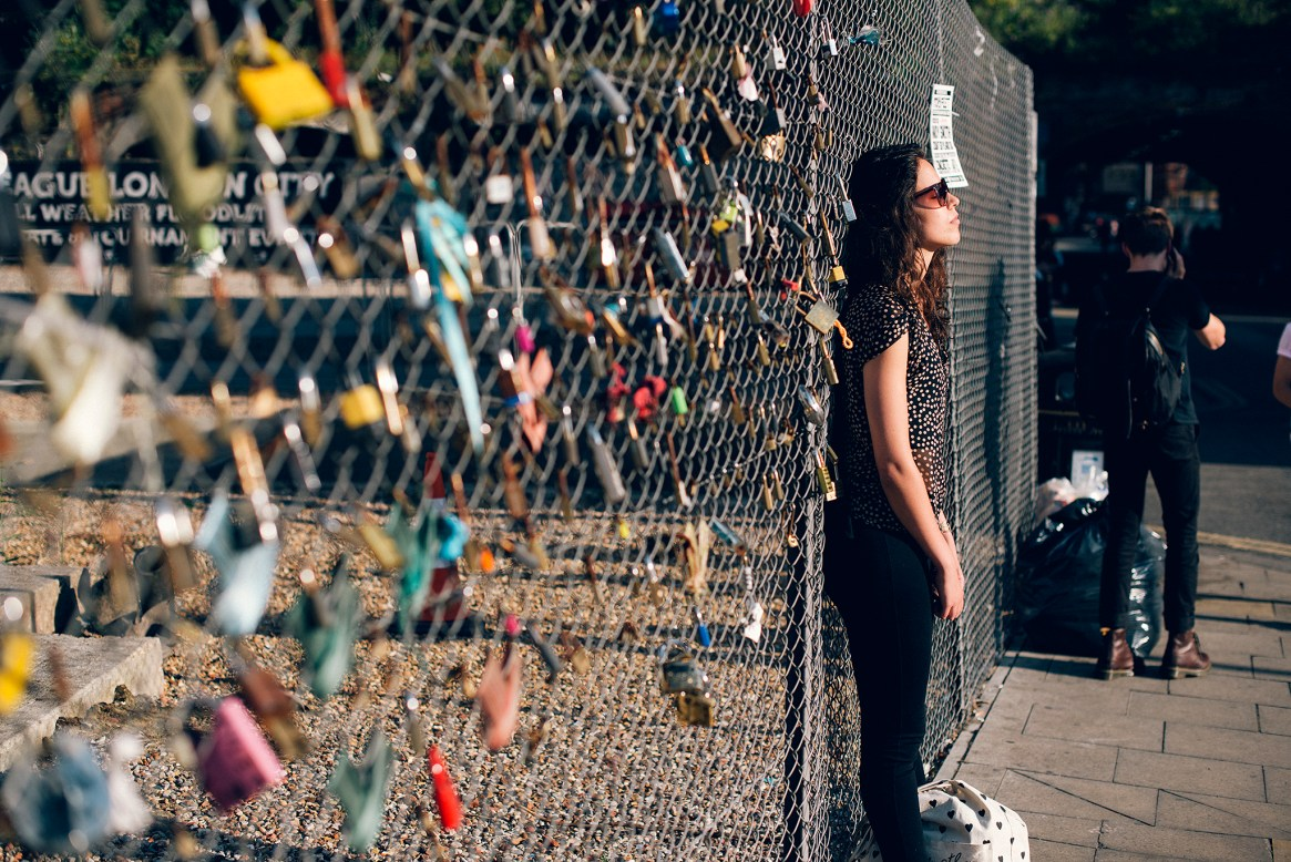 A woman stands with her eyes closed, leaning against a fence covered in love padlocks on a sunny late afternoon in Shoreditch, London