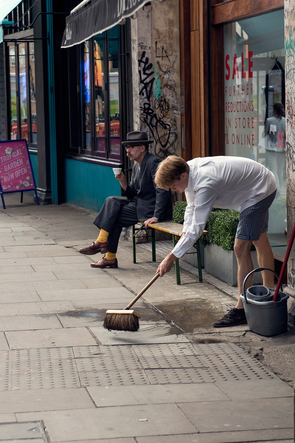 A young man sweeps the pavement in front of his shop, whilst another sits and sips on a cup of coffee