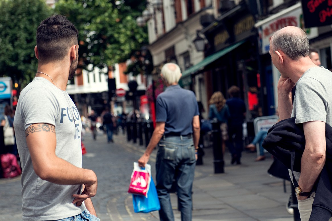 Two men turn back to look in unison at another walking down the street