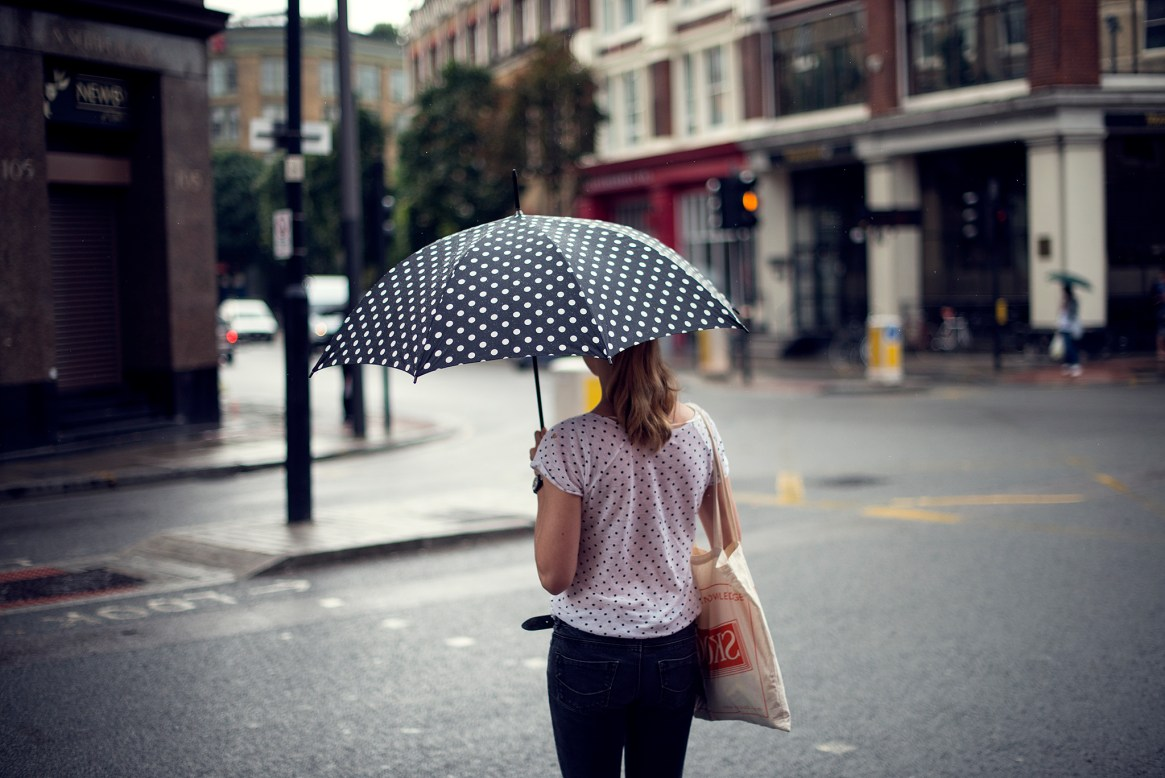A woman with black and white polkadot umbrella waits to cross the road