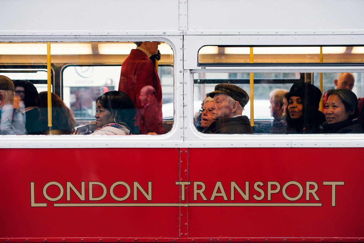 """A group of people seen through the window of a retro red and white tourist bus with sign reading"""" London Transport"""""""