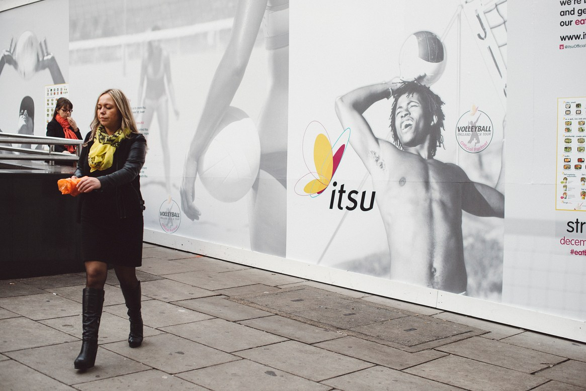 Two women dressed in black coats and coloutful scarves walk past a giant black and white poster showing volleyball players and coloured butterfly logo