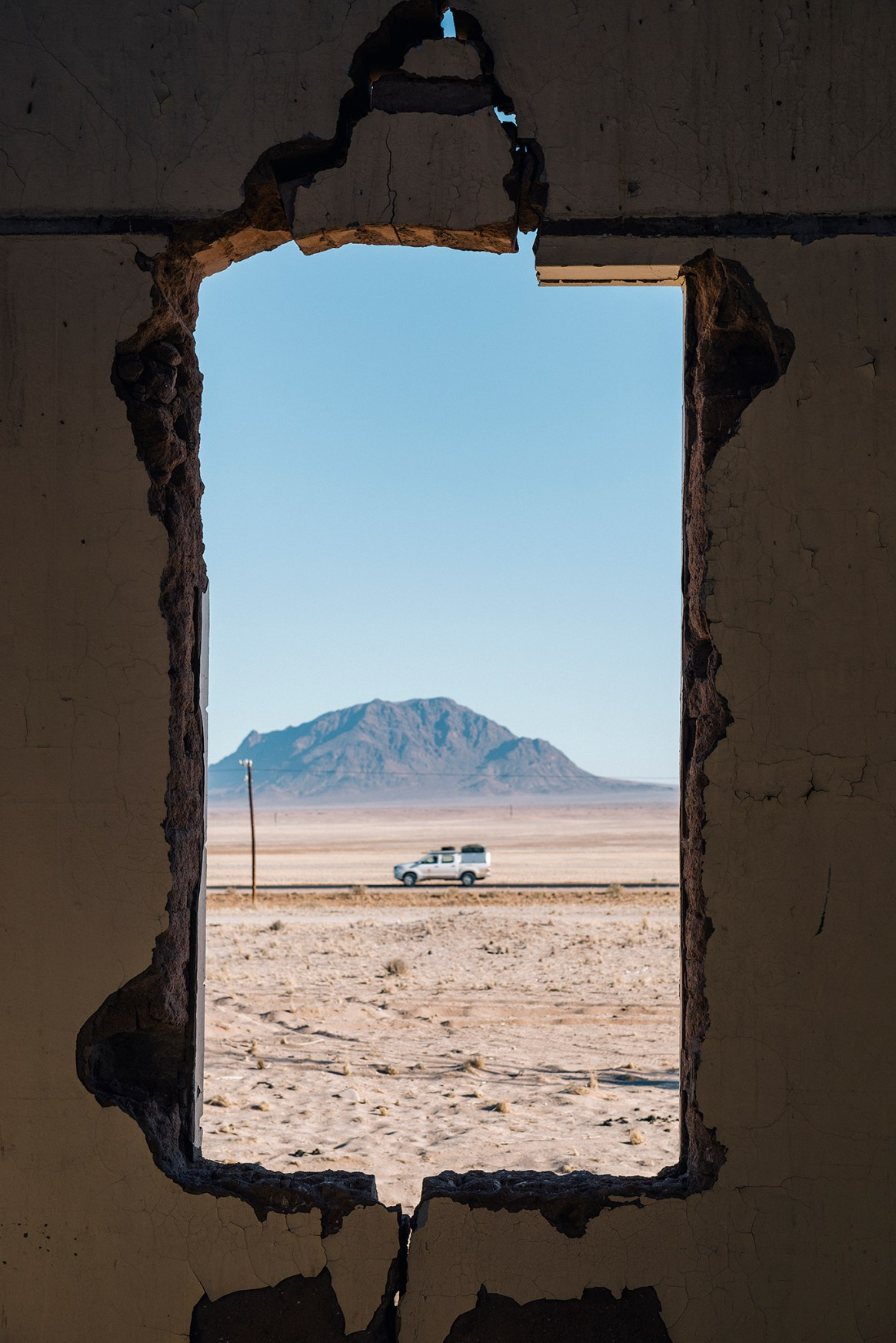 Shot of a car driving through the semi-desert with blue sky and mountains as a backdrop, seen through the creaking window of a derelict building at Garub, Namibia