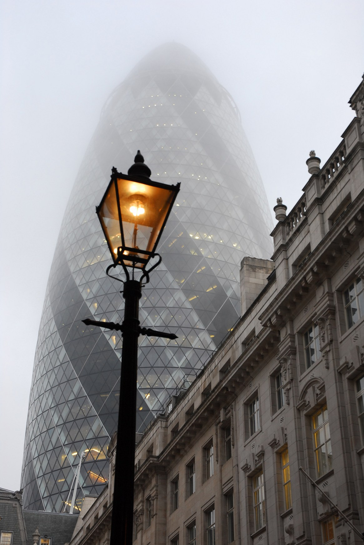 The Swiss Re building (aka The Gurkin) viewed from a misty alleyway, London