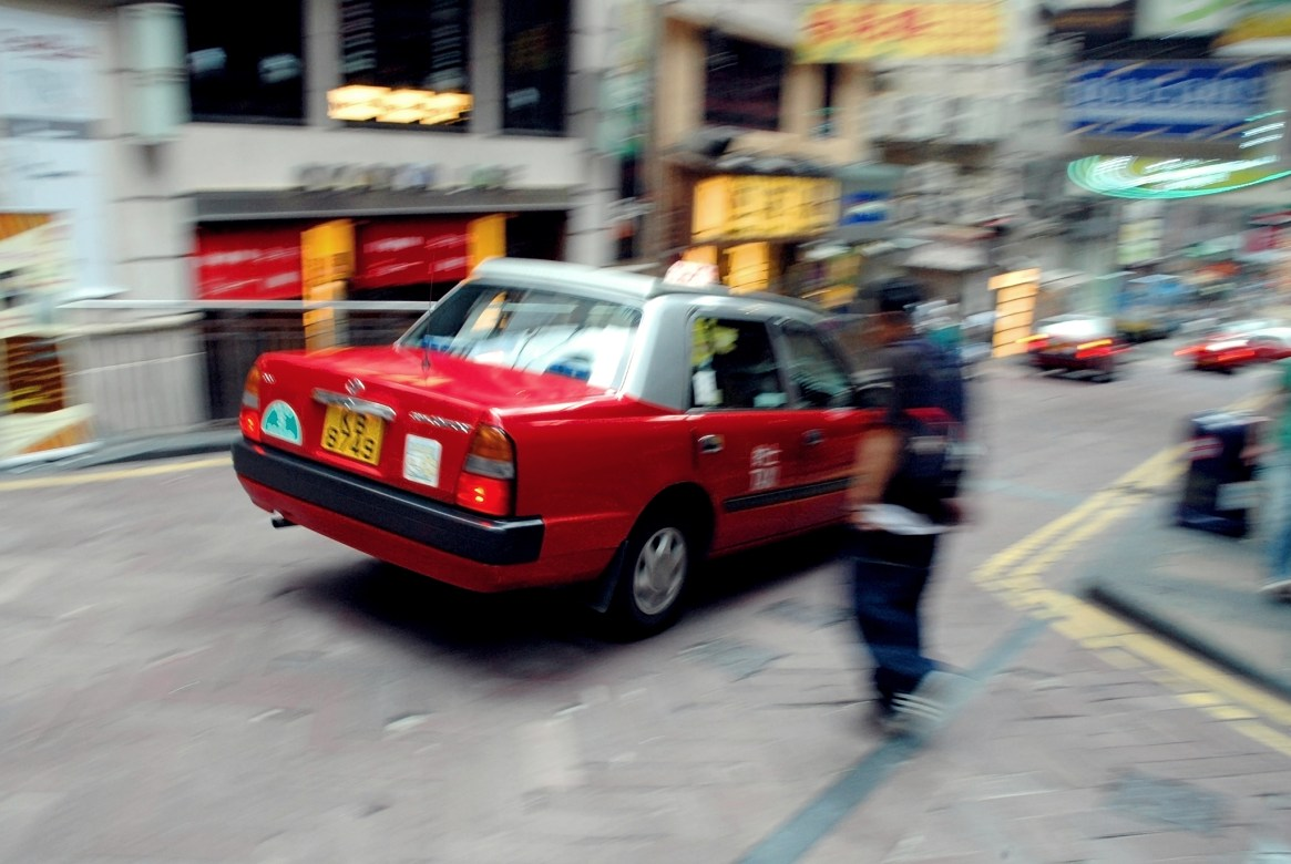 Red Hong Kong taxi speeding through a street in Lang Kwai Fong