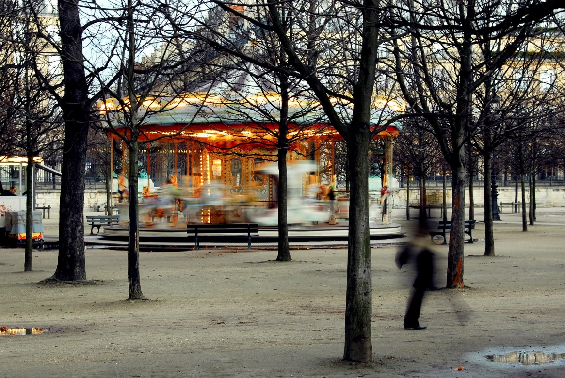 Spinning carousel and the silhouette of a woman passing by in the Jardin de Tuileries, Paris
