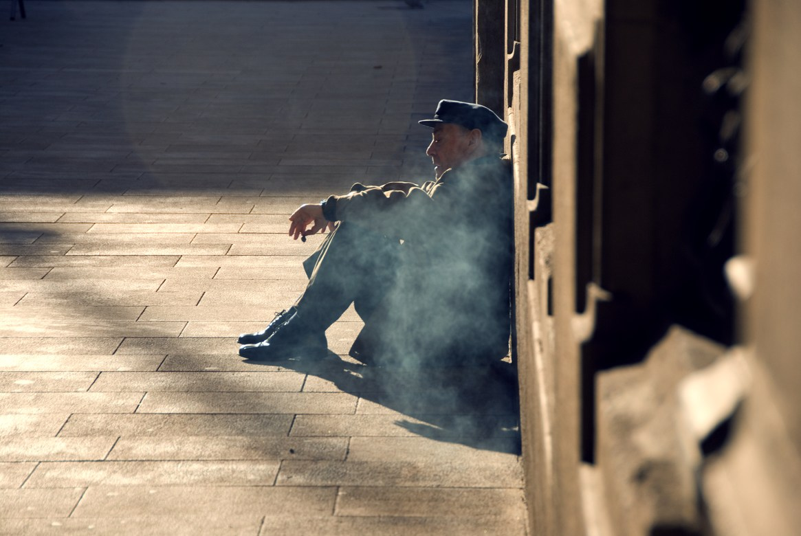 Old beggar in black, sitting in a haze of smoke on a pavement