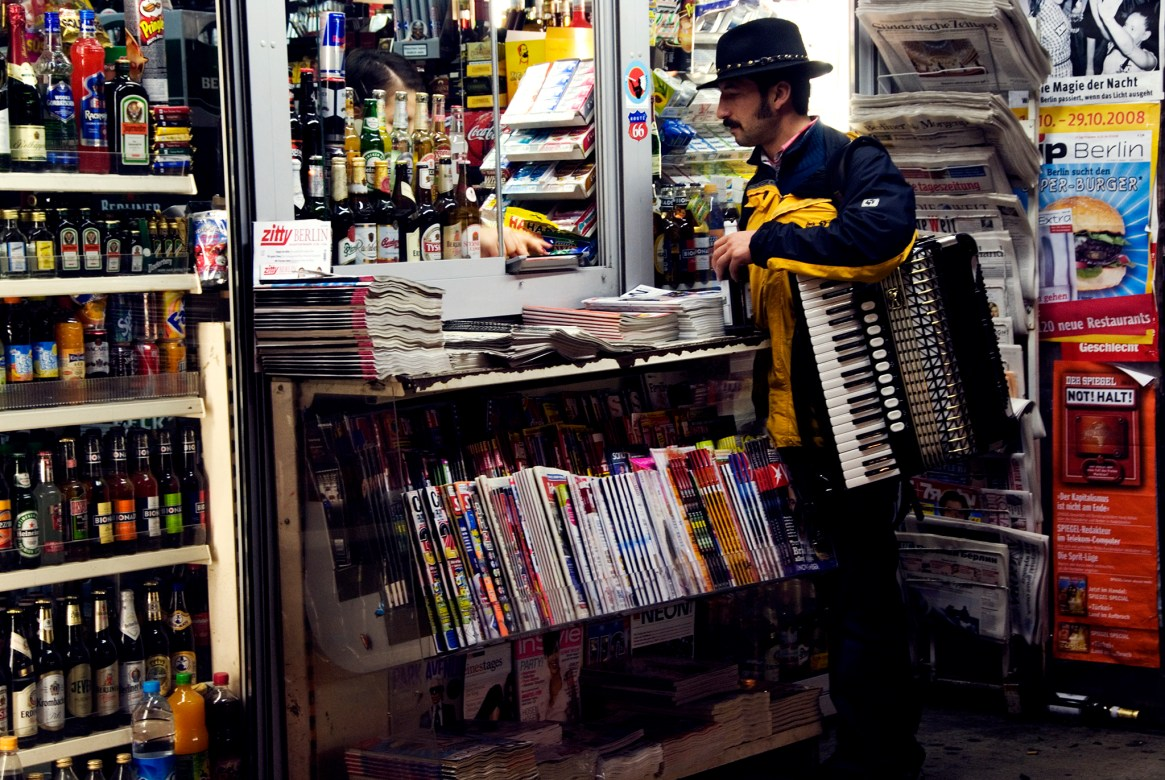 An accordian player buys refreshments at a newsstand stacked with magazines & bottles in Berlin