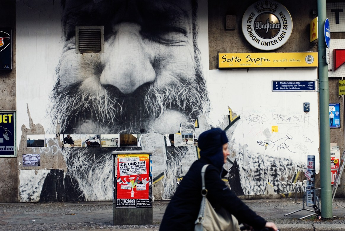 A woman in black coat on a bike rides past a roadside poster of a man with a comically large nose and moustache in Mitte, Berlin