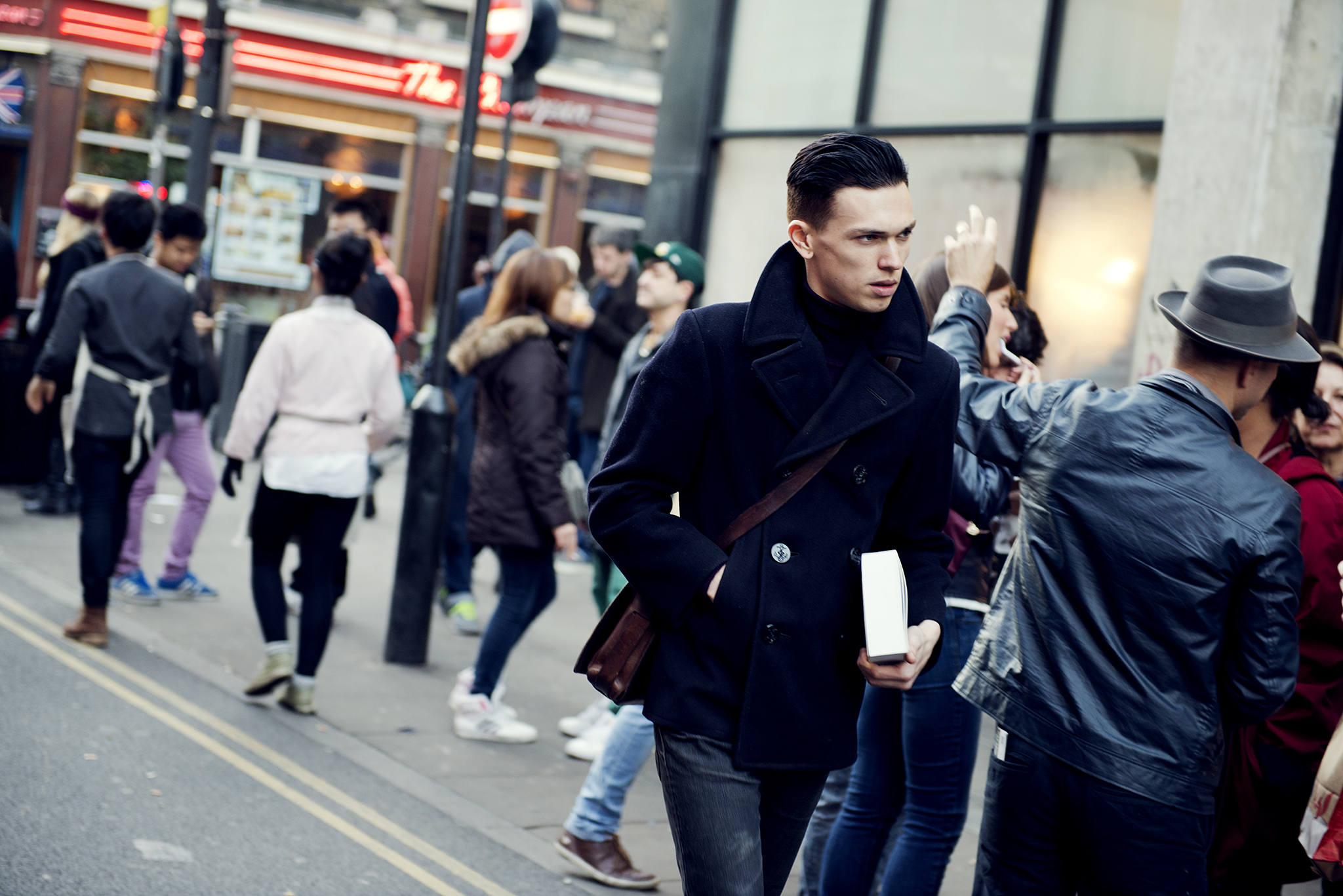 Young man in black coat with a book in his hand walking down Brick Lane