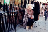 Woman in fur coat sitting by her market stall