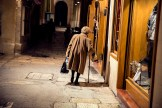 Old woman in grey coat walking down an alleyway at night