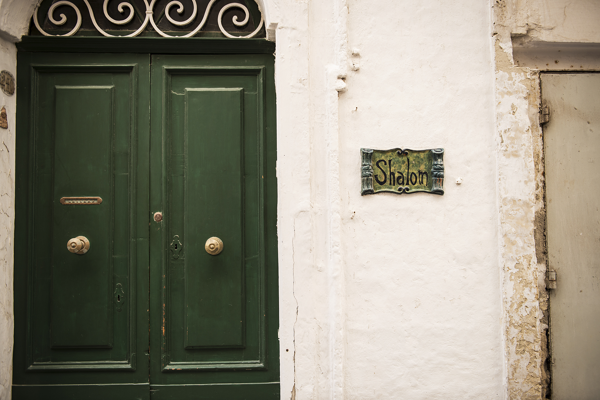 Green door, white wall and green sign