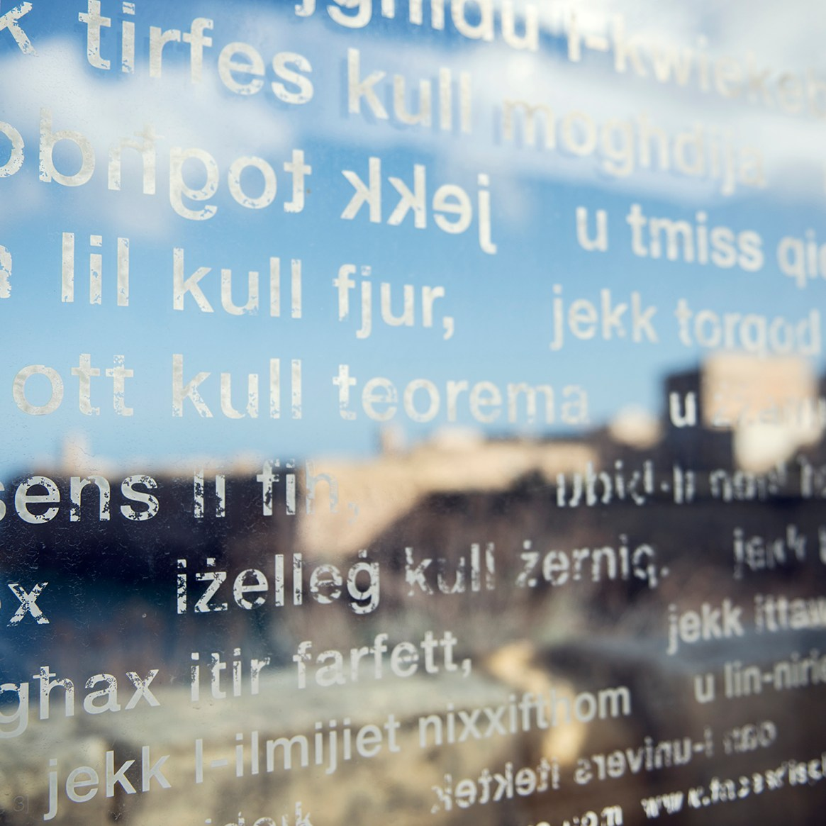 Malta old town seen through a pane of glass with text