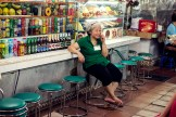 Woman in green resting on the green chairs in front of her market stall