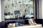 A woman lies and man sits resting in front of a semitransparent window of a shop with people inside