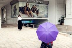 A woman with purple umbrella takes a picture of another woman posing on the pavement