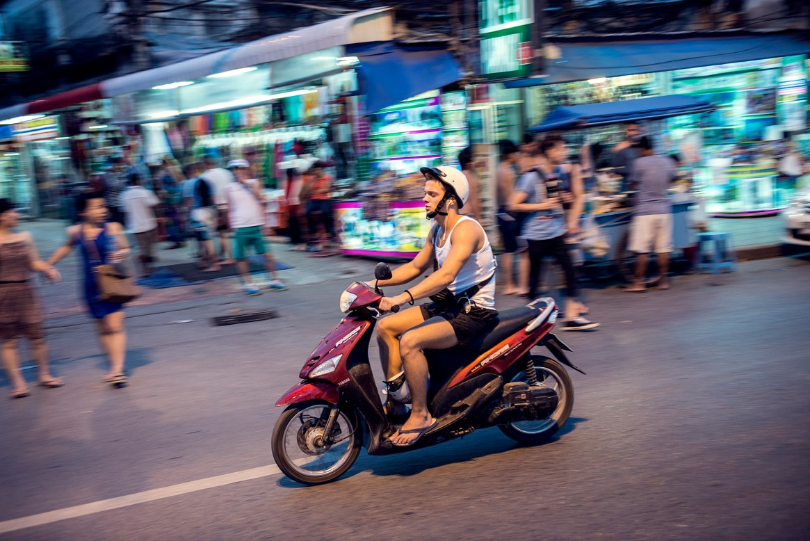 Young Westerner speeding on his motorbike in Patong