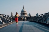 A woman wearing headphones and a bright neon outfit runs across the Millennium Bridge at sunrise, with St Paul's Cathedral in the background