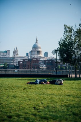 Two young men lie passed out on the grass outside of the Tate Modern gallery in London, with St Paul's Cathedral in the backround