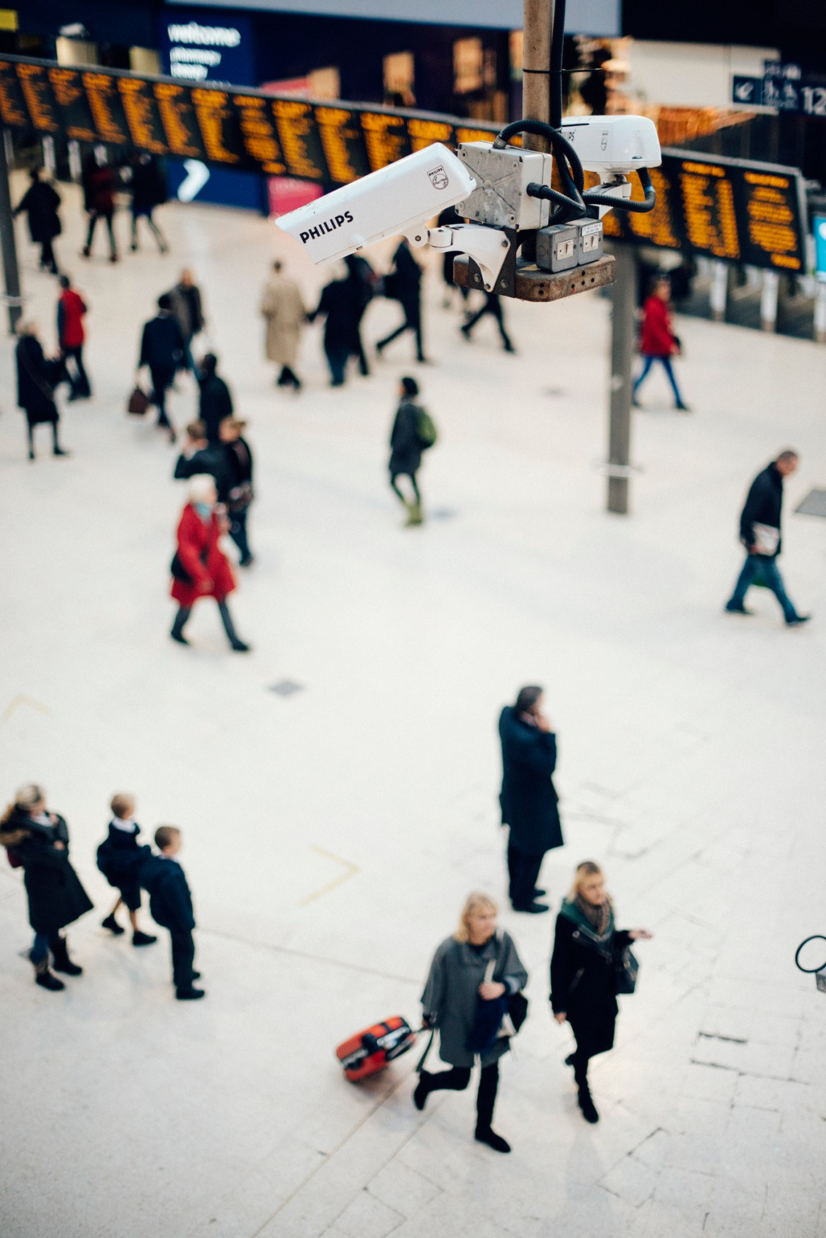 Wide shot showing a set of CCTV cameras recording proceedings with the small, blurry figures of commuters on the main concourse at Waterloo Station, London